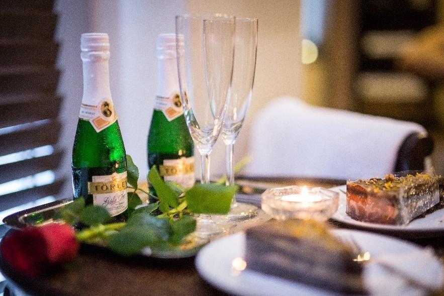 Egy üveg Törley pezsgő és poharak, ünnepi terítékkel